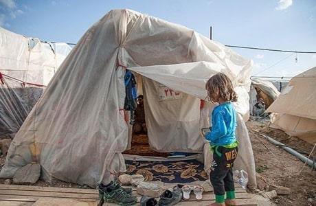 یک کودک از قربانیان زلزله در کنار چادر محل زندگیش